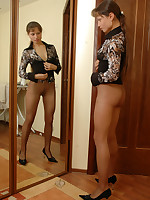 Attractive sweetie admires her lightly control top pantyhose in the mirror